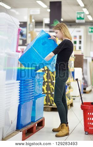 young blond woman buying in hardware store