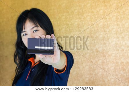 Close Up Asian Women Presenting Back Of Debit Or Credit Card With Blank Signature Area Focused At Th
