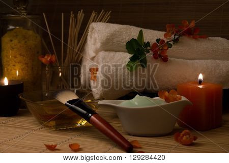 Close-up. Spa still life. Sea salt bath massage oil candles flowers and towels. Body Cream. Japanese Flowers.