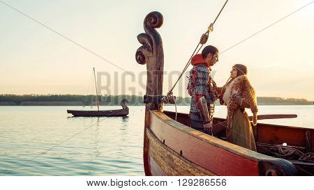 Couple of North princess and her beloved warrior on the bow of the sailboat.