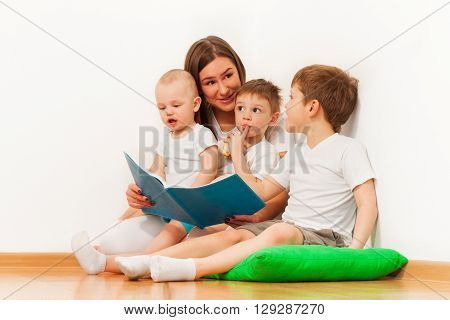 Young mother reading book to her three age-diverse kids, sitting on green pillow against white wall at the room