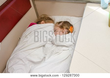 Two Children Sleep On The Train On The Same Ground Location In The Second-class Compartment Wagon