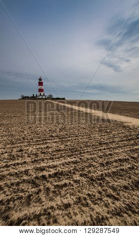 Lighthouse at Happisburgh, Norfolk, England with a ploughed field in the foreground