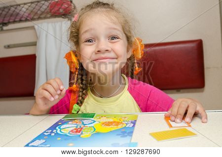 Little Girl On The Train With A Happy Smile Sitting At A Table On The Lower Second-class Place Car A
