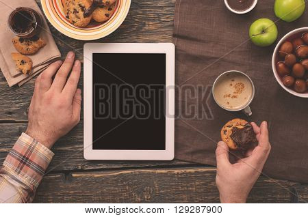 Man communicate via the Internet using the tablet while sitting at a wooden table in the morning. Male eating breakfast and communicating via the Internet using the tablet