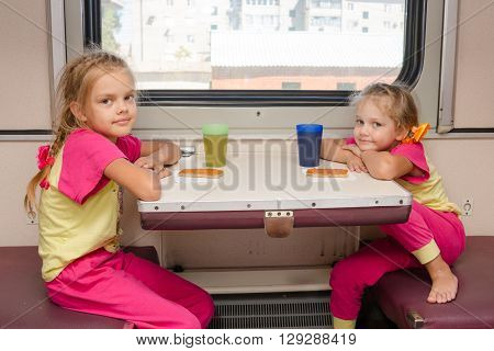 Two Little Girls On The Train Sitting At The Table In The Outboard Second-class Car In The Same Clot