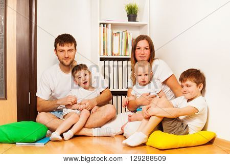 Big happy Caucasian family, mother, father and three age-diverse sons, sitting on the floor at home