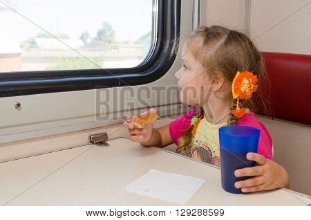 Little Girl Drinking Tea With A Sandwich On The Train At The Table On Outboard Second-class Carriage