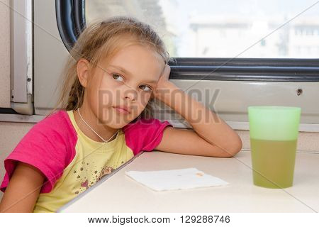Six-year Girl Thoughtfully And Tired Sitting On The Train At The Table In The Second-class Compartme