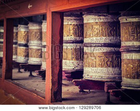 Vintage retro effect filtered hipster style image of Buddhist prayer wheels in Hemis gompa (Tibetan buddhist monstery). Ladakh, India