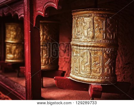 Vintage retro effect filtered hipster style image of Buddhist prayer wheels in Thiksey gompa (Tibetan buddhist monstery). Ladakh, India