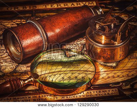 Travel geography navigation concept background - vintage retro effect filtered hipster style image of old vintage retro compass with sundial, spyglass and magnifying glass on ancient world map