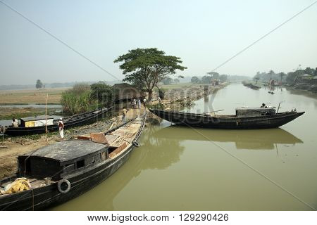 GOSABA, INDIA - JANUARY 14: wooden boat crosses the Ganges River January 14, 2009 in Canning Town, West Bengal, India.