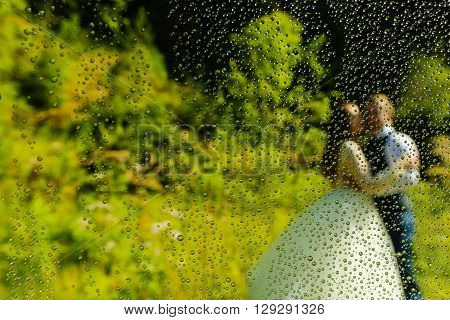 Groom And Bride Posing Trough A Wet Lense