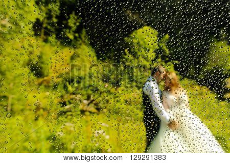 Bride And Groom Posing Outdoor Trough A Wet Lense