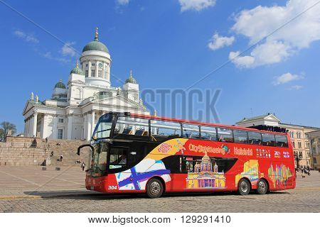 HELSINKI, FINLAND - MAY 10, 2016: Red double-decker Hop On Hop Off sightseeing bus waits for passengers at the Senate Square by Helsinki Cathedral. The visitor can hop on and off at any of the 15 main tourist attractions.
