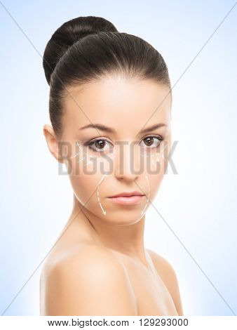 Portrait of beautiful, young woman with a perfect skin and arrows on her face. Face lifting, make-up, plastic surgery and skin care concept.