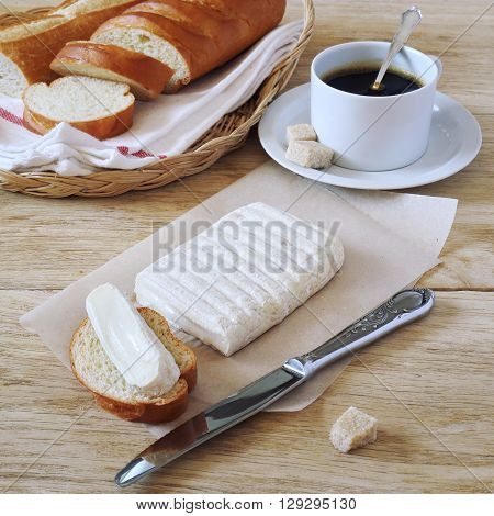 Breakfast: goat cheese baguette in wicker basket and cup of coffee