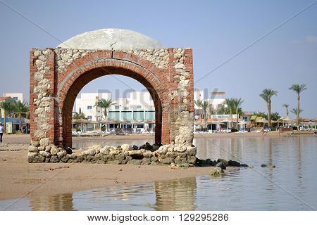 Disused old brick building in oriental style near water.