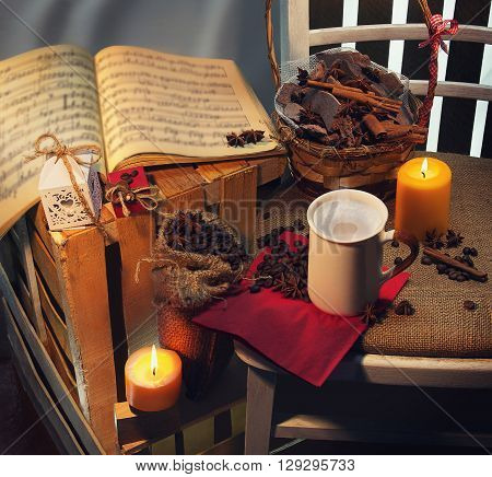 Still life. On a foreground is a white cup of coffee and coffee beans into the sack and two yellow candles on each side. On the background of burlap and wood are pieces of dark chocolate with cinnamon and star anise in a basket and leaf with notes and gif