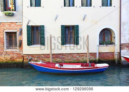 Boat near house on narrow canal in Venice, italy