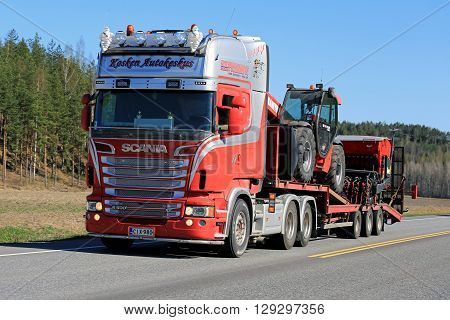 SALO, FINLAND - MAY 5, 2016: Red Scania semi truck hauls agricultural equipment on lowboy trailer along highway at spring in South of Finland.