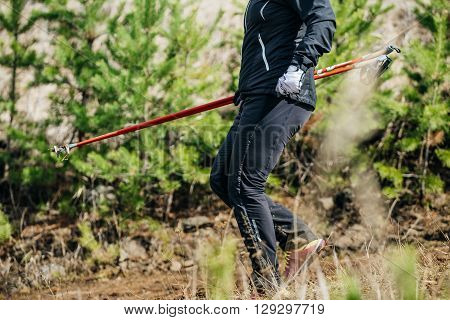 male runner with walking sticks down from mountain in forest