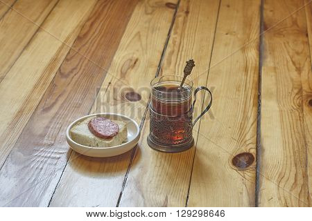 Composition with sandwich glass of tea and glass holder on floor