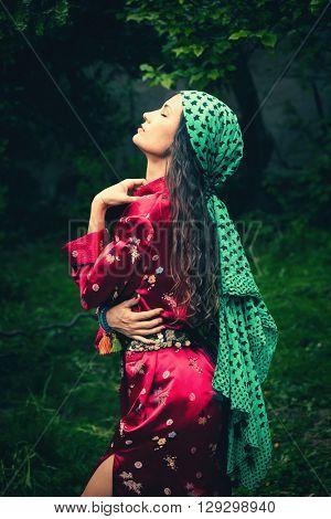 young woman in kimono and headscarf portrait in garden, profile