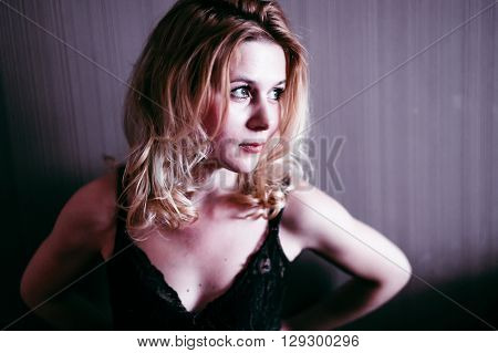 beautiful woman unbuttoning bra. pretty woman standing at the wall and seductively undresses. eyes looking away. selective focus