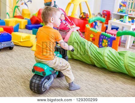 boy sitting on a toy motorcycle. child playing in a room with a lot of scattered toys