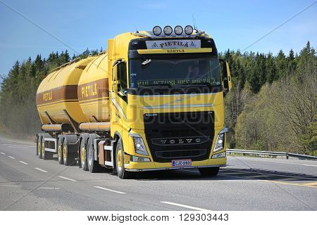 PARAINEN, FINLAND - MAY 6, 2016: Yellow Volvo FH tank truck for bulk transport moves along road in Southwest of Finland on a sunny day of spring.