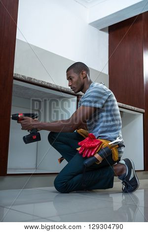 Manual worker drilling a hole in kitchen at home