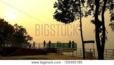 Nong Khai province Thailand- April 282016: Tourists walking on transparent sky walk to see view of Mekong River during sunset at Wat Pha Tak Suea. The first transparent sky walk in thailand.