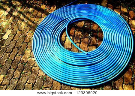 Blue plastic water hose roll on the brick floor