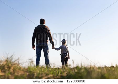Dad and son are in the sky and holding hands