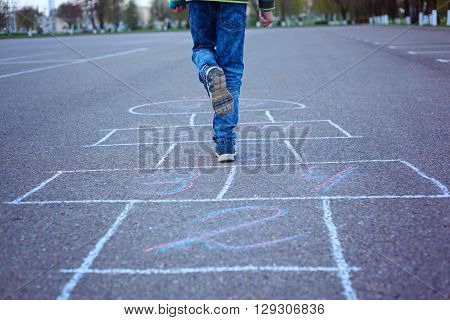 Kids playing hopscotch on the playground outdoors
