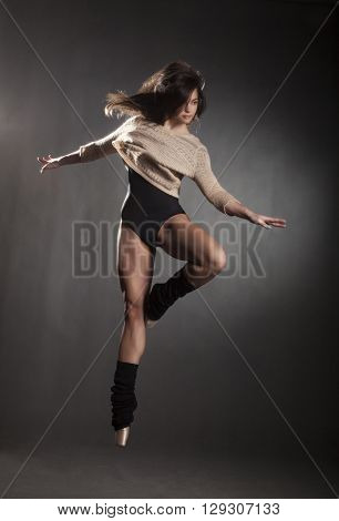 Young beautiful dancer in beige sweater and black leotard posing on a gray studio background