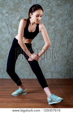 young sporty woman stretching the musles of legs