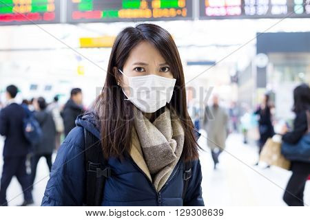Woman wearing face mask inside train station