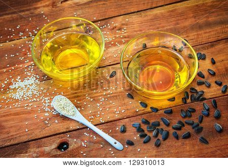 sesame and sunflower oil in glass bowls and seeds in a white spoon and on the wooden background