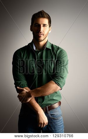 Handsome casual young man looking at camera and slightly smiling. Men's beauty. Studio shot over grey background.
