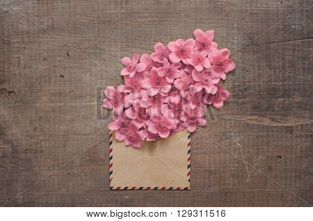 Wild flowers in the vintage envelope on wooden background