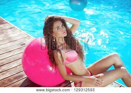 Beautiful Sexy Woman Model In Pink Bikini With Pilates Fitball Posing And Tanned By The Blue Swimmin