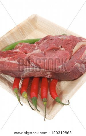 fresh raw red ribeye beef steak on bone over big light wooden plate isolated on white background with red and green hot chili pepper rib eye
