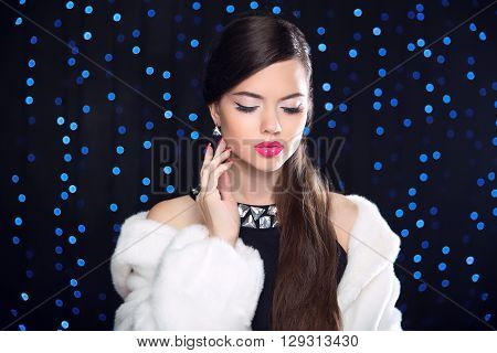 Makeup. Beauty Fashion Model Girl In White Mink Fur Coat. Elegant Brunette Woman  Posing Over Blue H