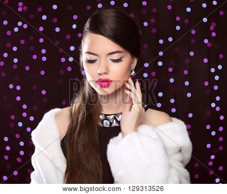Fashion Portrait Of Gorgeous Woman With Makeup In Luxurious Fur Coat Over Party Holiday Lights Backg
