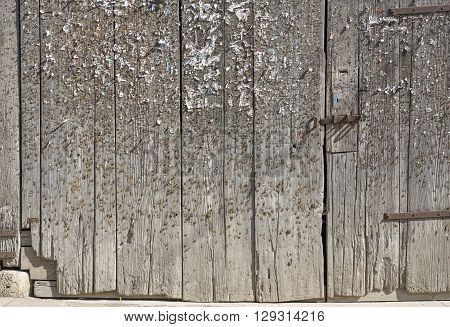 old weathered wooden gate blotched with lots of staples and pins