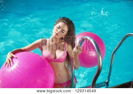 Pilates. Beautiful Girl Model Relaxing In Swimming Pool, Sexy Woman With Pilates Fitballs Posing In