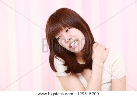portrait of portrait of young Japanese woman suffers from neck ache